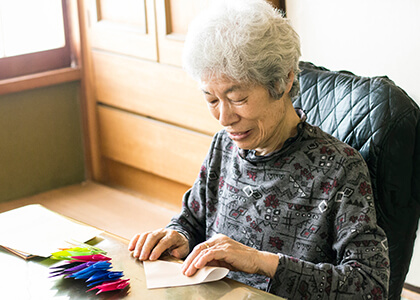 senior woman occupying her time with origami folding