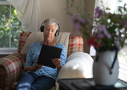 senior woman listening to an audio book