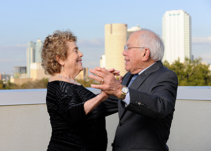 a senior couple dancing on the rooftop with a city skyline background