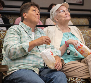 A resident and visitor enjoy a film in the private screening room